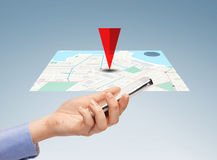 Close up of hand with smartphone and navigator map Royalty Free Stock Photos