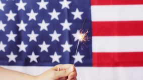 Close up of hand with sparkler over american flag stock video footage