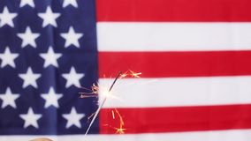 Close up of hand with sparkler over american flag stock video