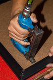 Close-up of hand stapling the photo frame. Close up of hand stapling the photo frame Royalty Free Stock Image