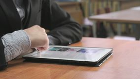 Student looking at photos using computer tablet. Close-up of hand of student boy dressed in black suit sits at desk at office the resting and looking at favorite stock video