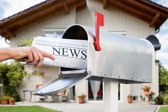 Hand Taking Newspaper From Mailbox. Close-up Of Hand Taking Newspaper From Mailbox In Front Of Their House royalty free stock image