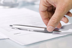 Close-up of a hand taking a pen to fill and sign documents. Royalty Free Stock Image
