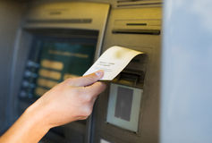 Close up of hand taking receipt from atm machine Royalty Free Stock Photos