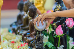 Close up hand of Thai people while bathing rite to buddha images. In Songkran festival on the April 13 annual ritual every year. Buddhist is bathing a Buddha Stock Photography
