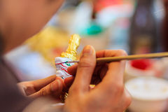 Close up hand of Thai sculptor during painting the masterpiece o Stock Images