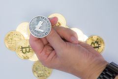 Crypto Currency Coin Flip. Close up of a hand about to flip a Litecoin coin royalty free stock photos