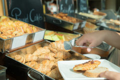 Close up of hand with tong taking bun at breakfast buffet in hot Stock Photography