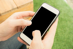 Close-up hand touch on phone mobile blank black screen outdoor lifestyle concept on blurry nature background stock photos