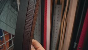 Unrecognizable person chooses a eco-leather belt in a store. Close-up of a hand that touches multicolored waist-belts hung in a self-service store. Man chooses stock video footage