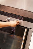 Close Up of Hand Turning Knob on Oven Stock Image