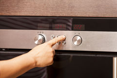 Close Up of Hand Turning Knob on Oven Royalty Free Stock Photos