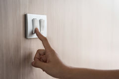 Close up hand turning on or off on grey light switch. With wooden background. Copy space stock photo