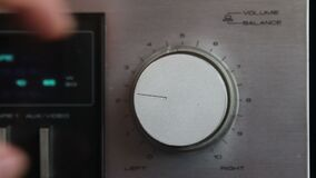 Close up of hand turning a volume knob on home stereo unit