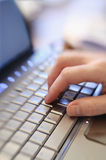 Close up hand typing on laptop computer keyboard Stock Photos