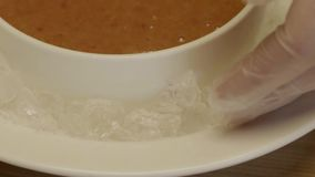 Cook put pieces of ice around the bowl stock footage