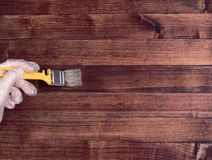 Close up hand use brush paint clear lacquer on the wood surface. royalty free stock image