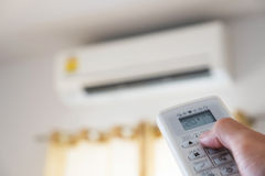 Close-up hand using remote control of air condition, selective focus Stock Photos