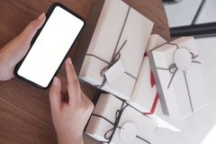 Close-up hand using smartphone for shopping online, gift box on table, shopping for presents royalty free stock photo