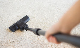 Close up of hand with vacuum cleaner at home Royalty Free Stock Images