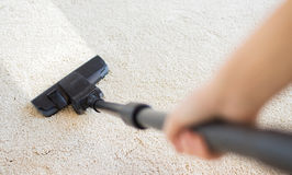 Close up of hand with vacuum cleaner at home Royalty Free Stock Image