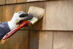 Close-up of hand wearing protective work gloves with brush paintbrush applying stain to cedar wood shingles exterior siding. Home. Hand wearing protective work stock photos