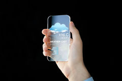 Close up of hand with weather app on smartphone Stock Photos