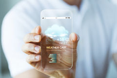 Close up of hand with weather cast on smartphone Stock Images