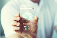 Close up of hand with weather cast on smartphone. Business, technology, weather cast and people concept - close up of male hand holding and showing transparent Stock Image