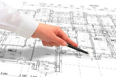 Close up of a hand in white shirt showing some details on the floor plan. Woman architect in white shirt showing some details on the floor plan layout with a pen Royalty Free Stock Image