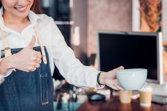 Close up hand of woman barista wear jean apron holding hot coffee cup and thumbs up served to customer at bar counter with smile royalty free stock photos