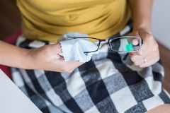 Close up of hand woman cleaning her glasses with cloth, clean lenses of eyeglasses