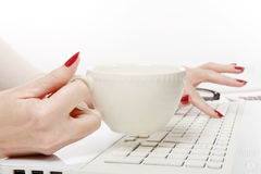 Close up of hand of woman with cup of coffee on desk Royalty Free Stock Images