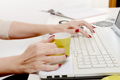 Close up of hand of woman with cup of coffee on desk Royalty Free Stock Photo