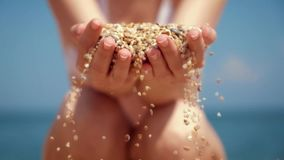 Close up of hand of a woman drizzling sea sand through her fingers stock footage