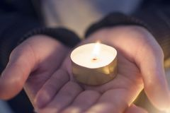 Close up hand of woman holdiClose up hand of woman holding lighting candles in the palm at theng lighting candles in the plam at t. Close up hand of woman Royalty Free Stock Image