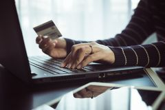 Close up of hand woman holding credit card and using laptop for online shopping concept. Close up of hand woman holding credit card and using laptop on desk for Royalty Free Stock Photography