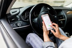 Close up hand of woman holding smartphone notification of car accident. Woman call emergency call while sitting the car. stock photo
