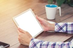 Close up hand woman holding tablet blank screen display on wood Royalty Free Stock Image