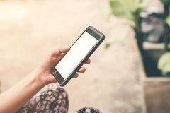 Close up hand woman holding and using phone in garden. Royalty Free Stock Images