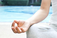Close up hand woman meditating in a lotus Yoga position at the pool spa Stock Photo