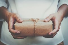 Close up hand woman present and holding kraft gift box packaging royalty free stock photo
