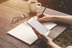 Close up hand woman writing notebook and holding phone on wood t Stock Images