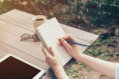 Close up hand woman writing notebook on wood table. Royalty Free Stock Photo