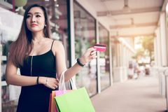 Close up hand of women holding credit card and shopping bags at shopping mall royalty free stock photography