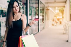 Close up hand of women holding credit card and shopping bags at shopping mall stock image