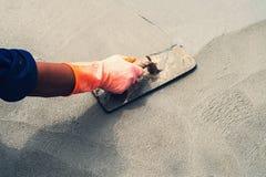 Close up hand worker leveling concrete pavement for mix cement a. T construction site Stock Photos