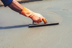 Close up hand worker leveling concrete pavement for mix cement a Stock Images