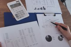 Close-up of hand working in office, studying using calculator and writing something with documents and chart on table royalty free stock images