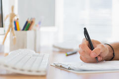 Close up of a hand writing in a modern office Royalty Free Stock Photo